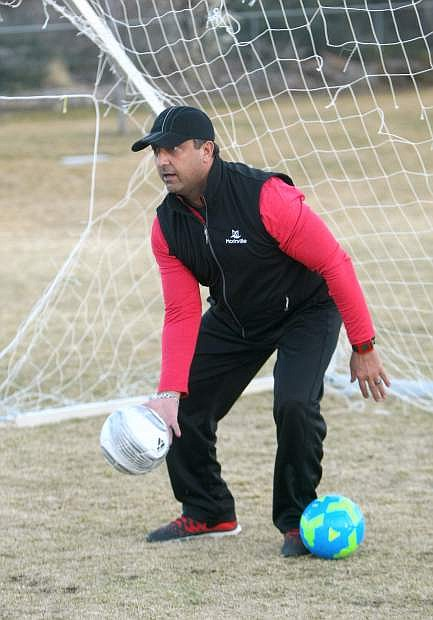 Soccer coach Ian Hill feeds balls to players during a kicking drill on Monday.