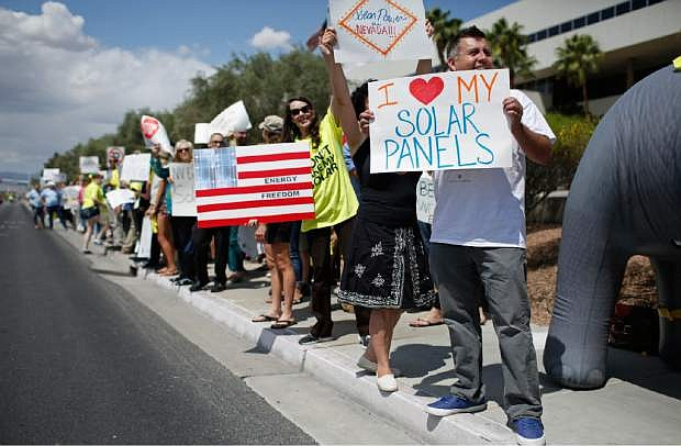 FILE--In this April 22, 2015, file photo, protestors, including Ronald Brittan, right, line up along the street during a rally in front of NV Energy in Las Vegas, Nev. The Nevada Supreme Court has decided not to allow a measure on the statewide ballot in November about rooftop solar electricity rates. Justices ruled Thursday, Aug. 4, 2016, that a referendum by opponents of a 2015 state law was fundamentally flawed. (AP Photo/John Locher, file)