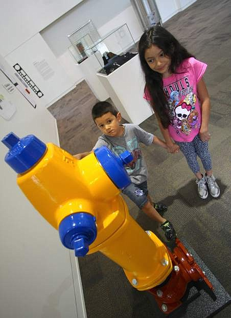 Daniela Alvarez Martinez, 9, and her 5-year-old brother Alem look at an American AVK fire hydrant that's on display at the Industrial Art exhibition at the Courthouse Gallery on Tuesday. The exhibit that embraces the area's design and manufacturing community is sponsored by the Capital City Arts Initiative. The gallery is open to the public Monday-Friday from 8 a.m. to 5 p.m.