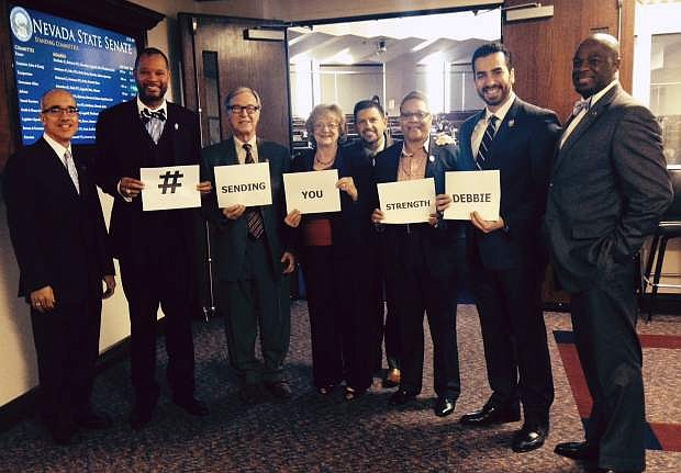 This photo taken Feb. 5, 2015 and provided by Peter Koltak shows, from left, Nevada Democratic Senators Mo Denis, Aaron Ford, David Parks, Joyce Woodhouse, Mark Manendo, Pat Spearman, Ruben Kihuen and Kelvin Atkinson posing for for a photo in Carson, Nev. The message is part of an informal social media campaign meant to encourage Sen. Debbie Smith, who was scheduled to receive surgery on a brain tumor on Feb. 6. (AP Photo/Peter Koltak)