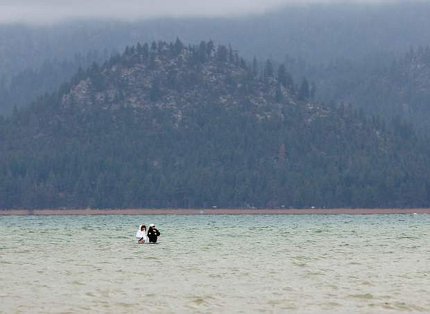At the 2014 State of the Lake presentation Thursday, Tahoe Environmental Research Center Director Geoff Schladow said the lake's water level will likely dip below its 6,223-foot natural rim within a couple months. In this photo taken earlier this month, two people walk in shallow water a couple hundred yards away from the shore.