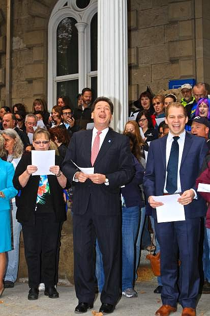 Lt. Governor Brian Krolicki leads a sizeable group of Nevadans in the singing of 'Home Means Nevada' on the State Capitol steps Thursday morning.