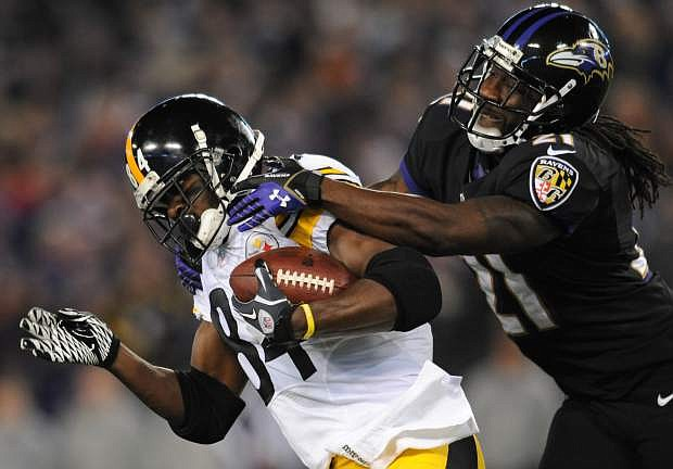 Pittsburgh Steelers wide receiver Antonio Brown, left, is tackled by Baltimore Ravens cornerback Lardarius Webb after getting a first down in the first half of an NFL football game on Thursday, Nov. 28, 2013, in Baltimore. (AP Photo/Gail Burton)