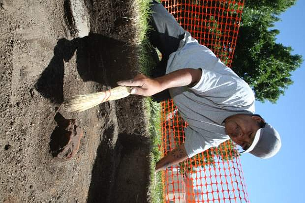 UNR student Lonnie Teeman clears sand away from a brick during an archaeological dig at Stewart Indian School.