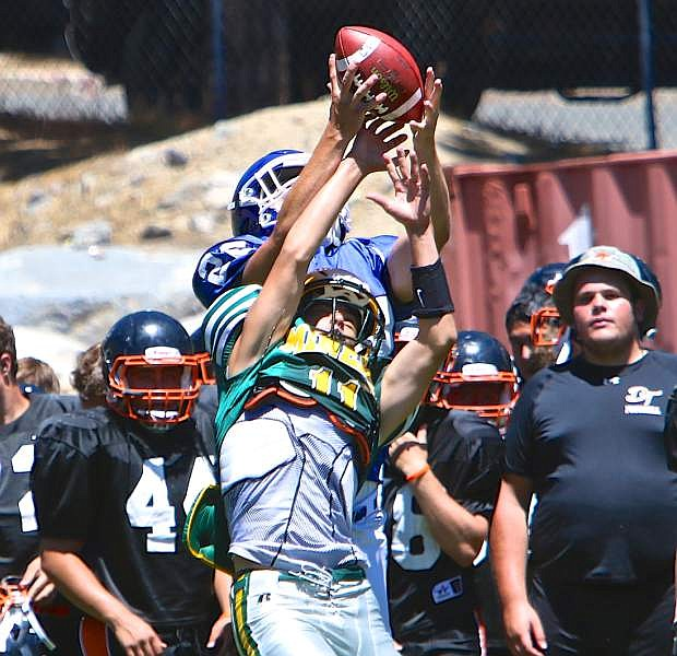 Carson senior Connor Quilling goes up for a reception against a Manogue defender on the 2nd day of summer training camp while Douglas players spectate from the sideline Wednesday at Incline High School.