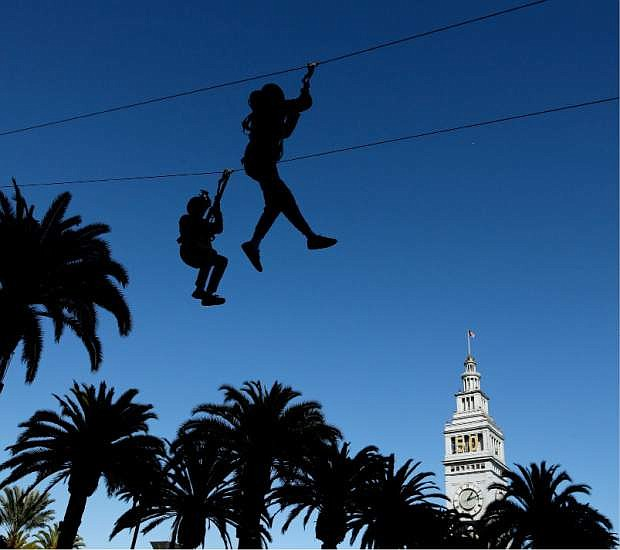 People dangle from a zip line at Super Bowl City Tuesday, Feb. 2, 2016 in San Francisco. The Denver Broncos play the Carolina Panthers in the NFL Super Bowl 50 football game Sunday, Feb. 7, 2015, in Santa Clara, Calif. (AP Photo/Charlie Riedel)