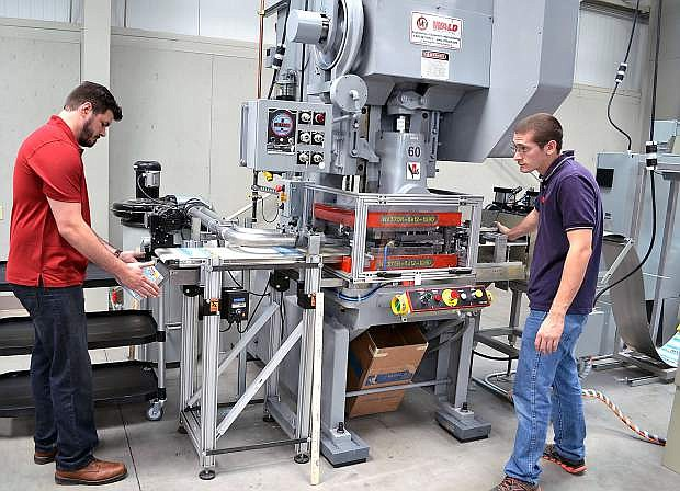 DMV tag plant employees Andrew Buskirk, red shirt, and Steven Leturgey test and adjust the tag plant stamping machine in preparation for opening the new factory July 6.