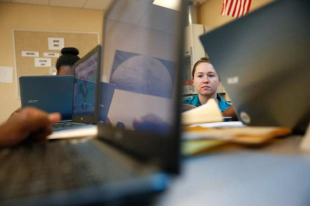 In this June 29, 2016, photo, Christine Steiner works with students at Rebel Academy in North Las Vegas, Nev. Rebel Academy, spearheaded by UNLV's College of Education, is a project to give prospective teachers hands-on experience during the summer. (AP Photo/John Locher)