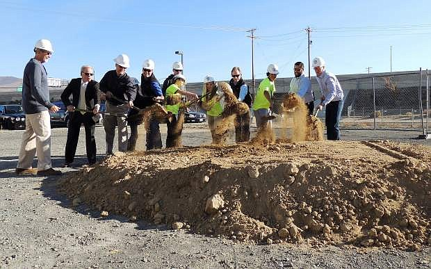 Club members, wearing yellow T-shirts, from the Boys & Girls Club of Western Nevada, from left, Autumn Cuellar, Sierra Machal and Julian Alvarado help break the ground at the new teen center on Friday morning.