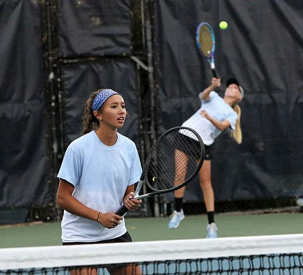 Emma Breeding serves and Anya Woodbury waits for their Bishop Gorman opponent's return volley at the NIAA State Championships at the Caughlin Club Friday.