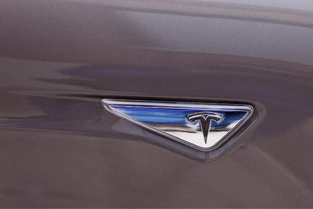 This Tuesday, April 7, 2015 photo, shows the Tesla logo on the automaker's Model S 70-D electric car, in Detroit. Tesla is going after mainstream luxury car buyers by boosting the range, power and price of its low-end Model S. The $75,000 all-wheel-drive 70-D can go a government-certified 240 miles per charge, has 514 horsepower and can go from zero to 60 in 5.2 seconds.  (AP Photo/Carlos Osorio)