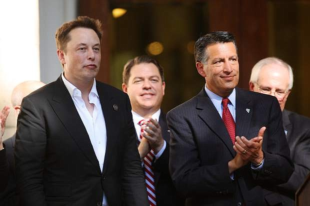 Tesla's Elon Musk, left, gets a standing ovation from Governor Brian Sandoval and the rest of the crowd at the State Capitol Thursday afternoon.