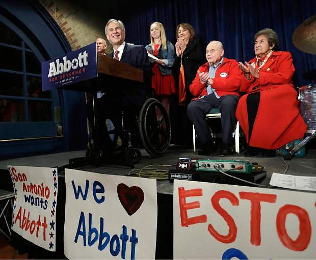 FILE - In this March 4, 2014, file photo, Texas Republican gubernatorial candidate General Greg Abbott, left, talks to supporters in San Antonio. Both Abbott and his Democratic opponent Wendy David are courting conservative voters and both support capital punishment. But Abbott is due, as attorney general, to issue a legal decision on whether the public can know where Texas gets its executions drugs. It's a dilemma that could put him in a difficult position with some voters _ and in a strange twist, one that Davis can't easily exploit. (AP Photo/Eric Gay, File)