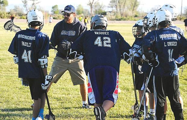 Oasis lacrosse coach John Keitz provides instructions to several players during Tuesday's practice.