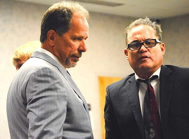 Kevin Travis, left, and attorney John Routsis prepare Tuesday in District Court for Kevin and Levi Travis' sentecing hearing.