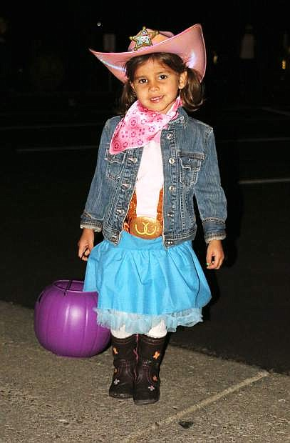 Nevaeh, 3 1/2, dressed as Disney's Sheriff Callie, smiles during the Trunk or Treat event Friday night at the Nevada Appeal. About 200 families turned out for the event where trick-or-treaters can collect candy from trunk to trunk.In addition to trick-or-treating, the  event featured games, raffle prizes, pumpkin carving and prizes for best costume and best decorated trunk.