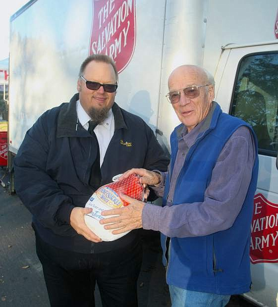 Lt. Mark Cyr with the Salvation Army accepts a turkey donation from Carson City resident Richard Long during the Salvation Army's annual turkey drive in front of Mike's Pharmacy on Tuesday.
