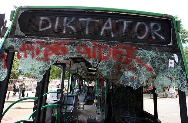 People observe a destroyed urban bus, with broken windows and the destination sign reads ''This bus goes to Dictator'' at the Taksim square in Istanbul on Thursday, June 6, 2013. Turkish officials, scrambling to contain tensions, have delivered more conciliatory messages to thousands of protesters denouncing what they say is the government's increasingly authoritarian rule and its meddling in lifestyles. (AP Photo/Thanassis Stavrakis)