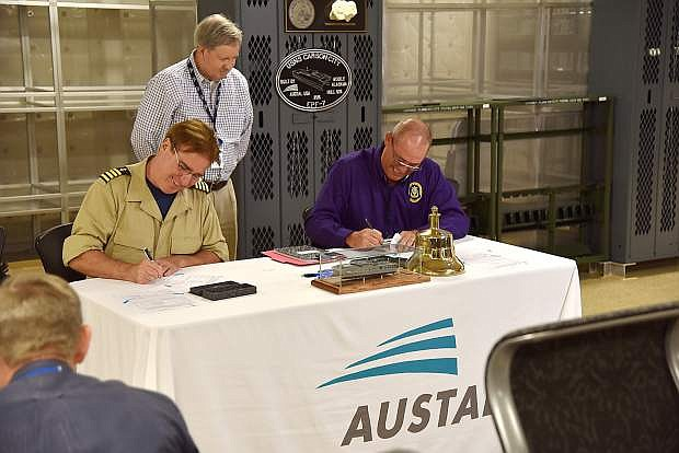 USNS Carson City Captain Robert Wiley, left, Austal EPF Contracts Manager Tommy Jordan, standing, and SUPSHIP GC Rep John Hessin are seen on Friday.