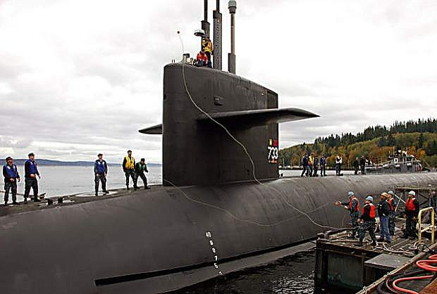 The Ohio-class ballistic-missile submarine USS Nevada (SSBN 733) receives mooring lines from shore as it prepares to dock at Naval Base Kitsap following a strategic deterrent patrol. The U.S. Navy is constantly deployed to preserve peace, protect commerce, and deter aggression through forward presence.