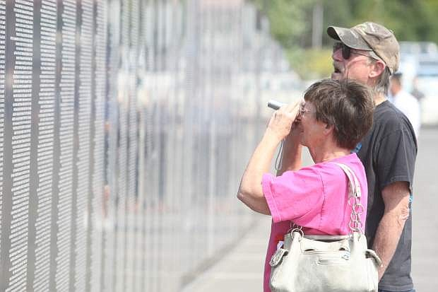 Tim Terry of Reno looks on while Patti Elder of Sparks takes a picture of Terry's friend's name on the Vietnam Traveling Memorial Wall in Virginia City on Saturday.