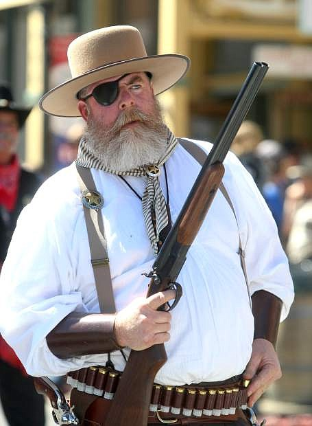 A member of the Virginia City Vigilance Committee prepares to reload his shotgun while walking in the annual Labor Day parade on Monday.