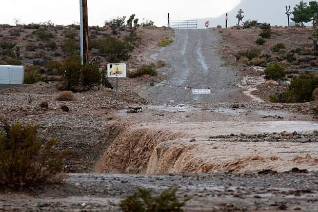 Violent flooding washes out a driveway near on Kyle Canyon Road at  Mount Charleston near Las Vegas on Sunday, Aug. 25, 2013.  Heavy rains forced closure of the road Sunday afternoon. (AP Photo/Las Vegas Review-Journal, Jessica Ebelhar)