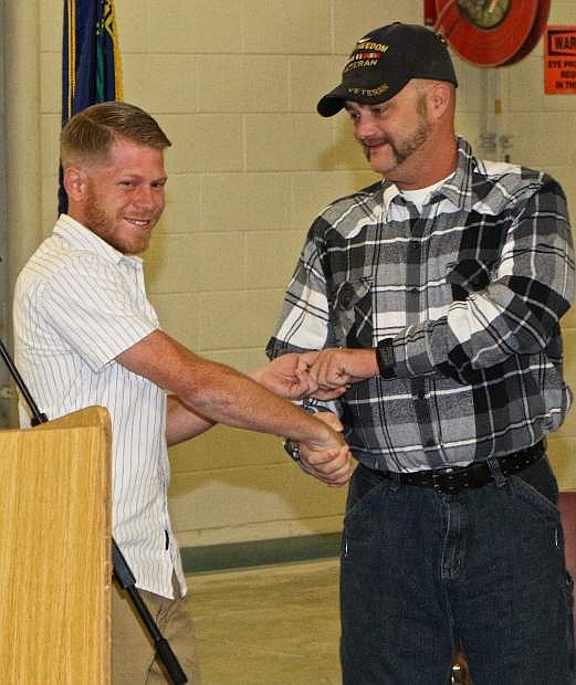 Veteran Michael Atkinson, the last recipient of a vehicle from the Recycled Rides program at WNC, presents the keys to latest veteran recipient Joseph Davis Alton III Wednesday morning at Western Nevada College.