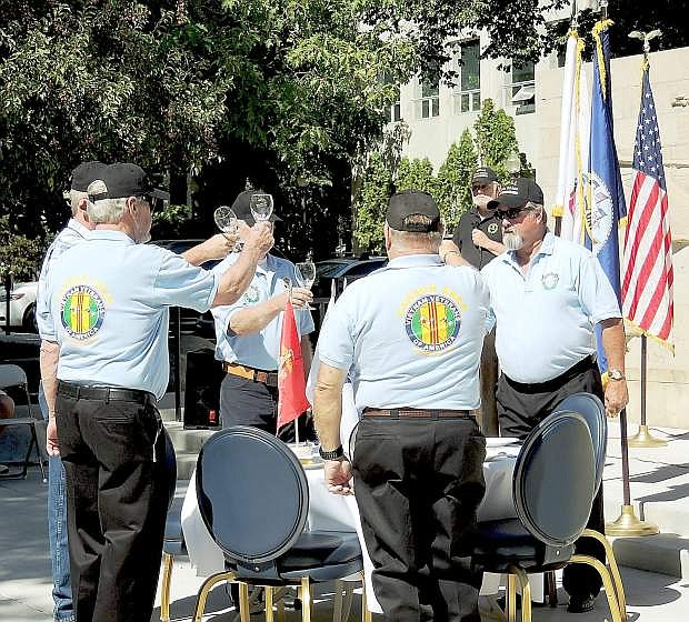 Members of The Vietnam Veterans of America-Carson Area Chapter 388 perform the Missing Warrior Table and Honors Ceremony after remarks by Mayor Robert Crowell and others at the Nevada State Veterans Memorial.