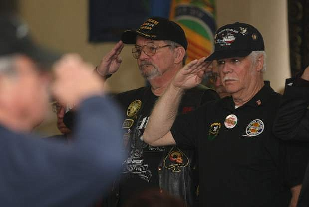 Rick Arnold, president of the Carson Area Chapter 388 of the Vietnam Veterans of America, and other veterans salute during Taps at the Vietnam Veterans Day Rememberance Ceremony on Saturday at the Carson Nugget.