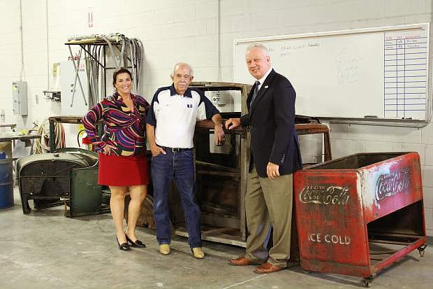 Western Nevada College Foundation board member Amy Clemens and Garth Richards, owner of Silver Oak Golf Course, and WNC President Chet Burton inspect some of the $15,000 worth of classic auto parts at the WNC auto body shop donated to the Foundation by Richards.