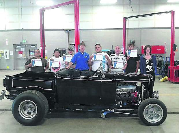 Johnnie Erwin, Samuel Simmons, Levi Greer, instructor Jason Spohr, Alan Bill, John Hull, Ethan Galloway and Trade Adjustment Assistance Community College & Career Training grant manager Linda Devon pose with a 1932 Ford Roadster with their certifications.
