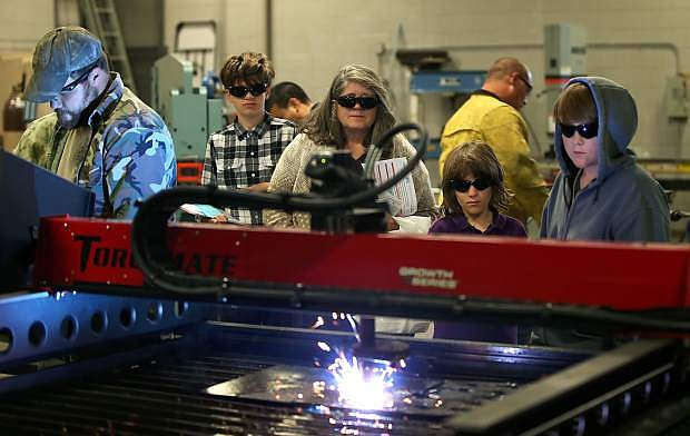Jon Bezzone, far left, demonstrates a laser plasma cutter to a group of visitors during Manufacturing Day at Western Nevada College on Thursday.
