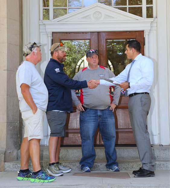 Cesar Melgarejo, right, Veteran's Policy Analyst for the Governor meets with Route for the Brave participants Kevin Winton, David Roth and Darin Fishburn on the steps of the Capitol building Monday. Winton and Roth are walking across the United States to raise awareness and money for veterans.
