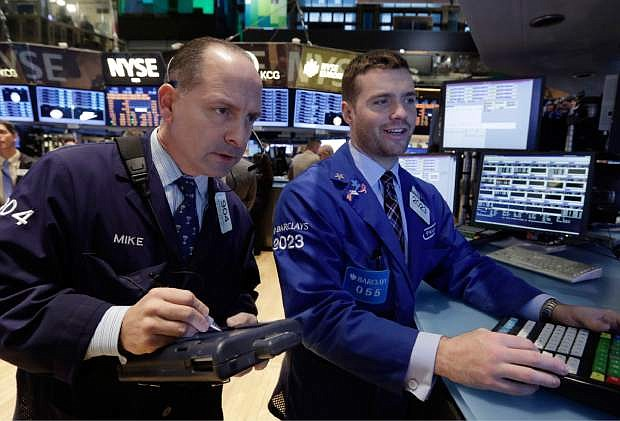 Traser Michael Urkonis, left, and specialist Frank Masiello work on the floor of the New York Stock Exchange Monday, Dec. 9, 2013. The stock market is opening little changed following last week's strong U.S. jobs report. (AP Photo/Richard Drew)