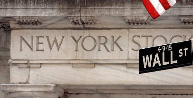 FILE - In this May 11, 2007 file photo, a Wall Street sign is seen at an entrance to the New York Stock Exchange. Three years after President Barack Obama signed a sweeping overhaul of lending and high-finance rules, implementation of the law is behind schedule with scores of regulations yet to be written, let alone enforced. Obama was meeting with top banking regulators Monday, Aug. 19, 2013, for a status report with the five-year anniversary of the financial meltdown approaching this fall. (AP Photo/Richard Drew, File)