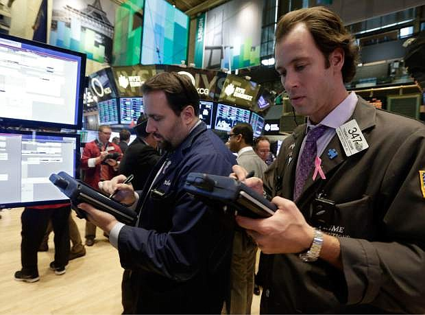 Thomas Cicciari, right, works with fellow traders on the floor of the New York Stock Exchange Monday, Nov. 18, 2013. The Dow Jones industrial average crossed 16,000 points for the first time early Monday and the Standard & Poor's 500 index crossed 1,800 points. (AP Photo/Richard Drew)
