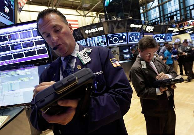 Trader Jonathan Corpina, left, works on the floor of the New York Stock Exchange Monday, July 8, 2013. Stocks rose in early trading Monday ahead of the start of second-quarter corporate earnings reports. (AP Photo/Richard Drew)
