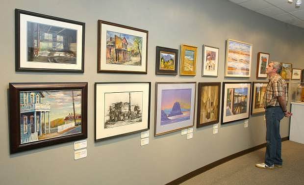 Joe Paslov, an administrative assistant with the Nevada Arts Council views the art collection of Wally Cuchine that is on display at the council's office.