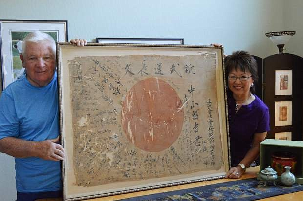 Carson City Host Lions Club member, Sam Herceg, left, displays a historical Japanese war flag with his wife, Ayako, right, purchased from vintage shop Kaleidoscope at 210 S. Carson St.