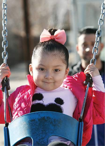 Valerie Ayala, 4, smiles while swinging in the warm sunshine on Monday afternoon at Mills Park.