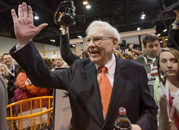 Investor Warren Buffett greets shareholders while touring the exhibit floor prior to holding the Berkshire Hathaway shareholders meeting, in Omaha, Neb., Saturday, May 4, 2013. Tens of thousands attend Berkshire Hathaway shareholder meeting to hear Warren Buffett and Charlie Munger answer questions for more than six hours. No other annual meeting can rival Berkshire's, which is known for its size, the straight talk Buffett and Munger offer and the sales records shareholders set while buying Berkshire products. (AP Photo/Nati Harnik)