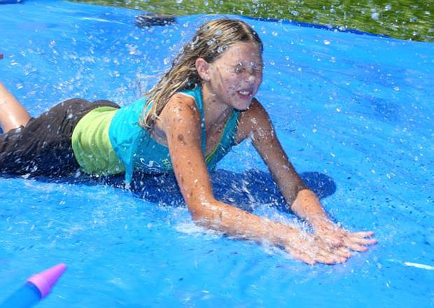 Keeping cool on a hot summer day, Boys & Girls Clubs of Western Nevada member Mekenna Zorn, 12, takes a dive onto a water slide Monday.