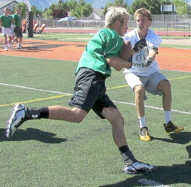 Fallon's Cameron Matzen runs into a Bishop Manogue defender during their 7-on-7 tournament game Friday at Douglas High School.
