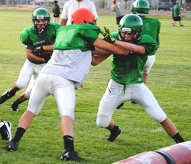 Fallon junior running back Nathan Heck, left, runs through the line during a drill. The Greenwave finished third last season in the Northern Division I-A.