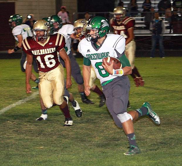 Fallon quarterback Joe Pyle keeps the read-option and runs past Sparks' Moises Collazo in the first quarter.