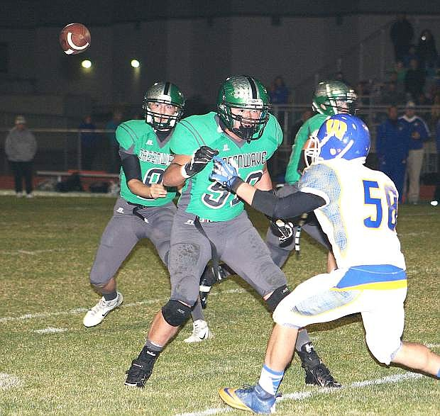 Fallon quarterback Morgan Dirickson, left, throws a pass as lineman Kenny Keyes, middle, blocks during last week's 21-14 loss to Lowry. The Greenwave are the No. 1 seed for the Northern Division I-A playoffs and host No. 4 Fernley at 7 p.m. today at the Edward Arciniega Complex.