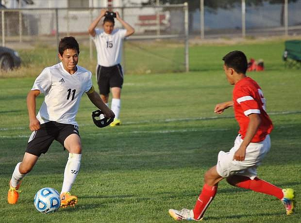 Luis Orozco (11) of the Wave charges through the Wolverines during their Friday match.