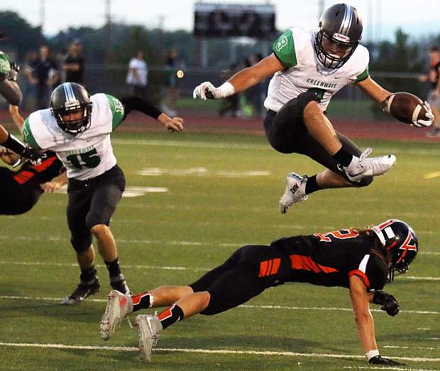 Fallon's Connor Nelson leaps over a Fernley defender in the Wave's season opener, a rivalry game against the Vaqueros.