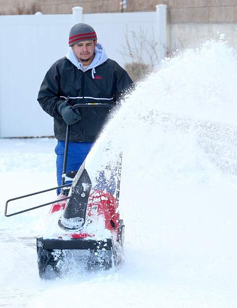 Juan Hernandez with Lawn Pro maintenance snowblows a customer's driveway on Tuesday. Today's forecast calls for clear skies, but for extreme cold with a high aroud 20 degrees and overnight lows around 5.